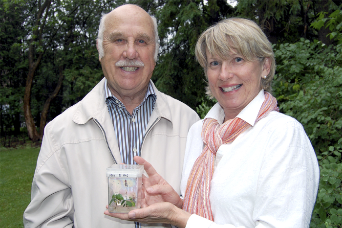 Two people holding a plant jar