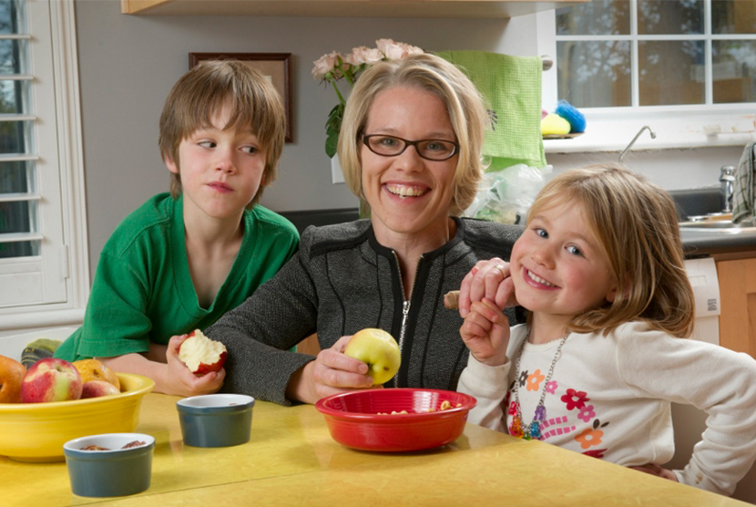 Mom with two kids eating apples at table