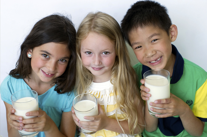 Three children holding glasses of milk