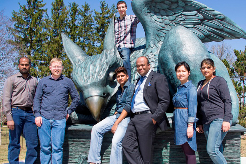 faculty and students posing with gryphon statue