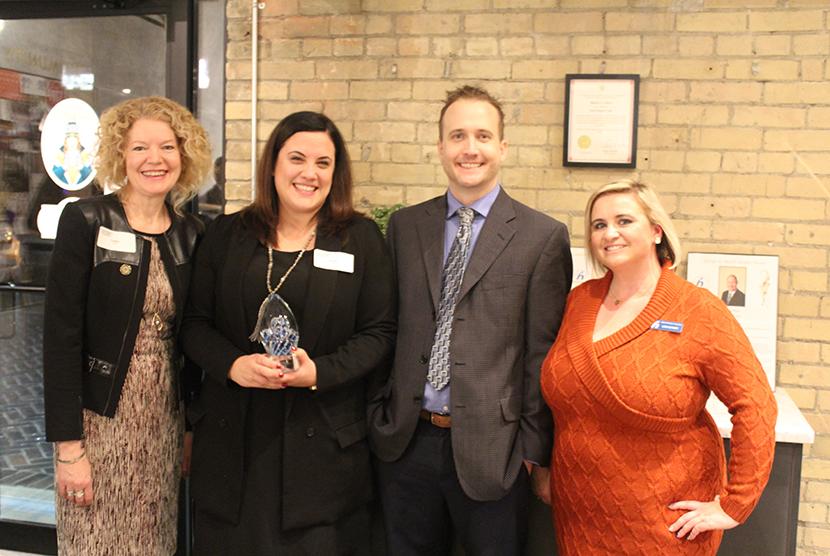 photo of winner with members of alumni association