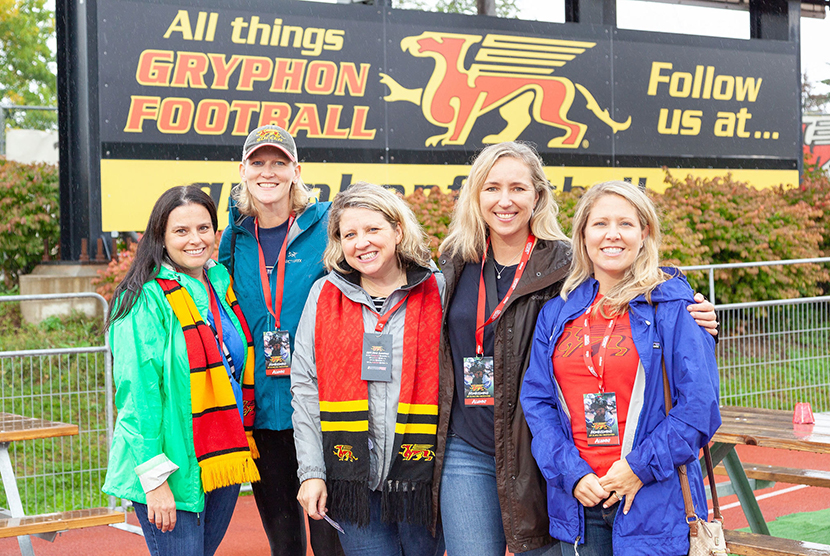 alumni smiling in front of scoreboard
