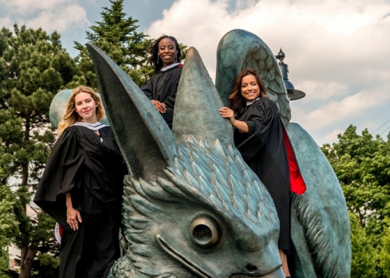 3 students on gryphon statue in convocation wear