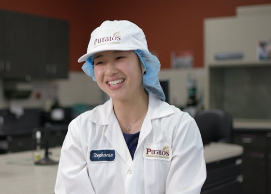 girl smiling with food safety clothes on