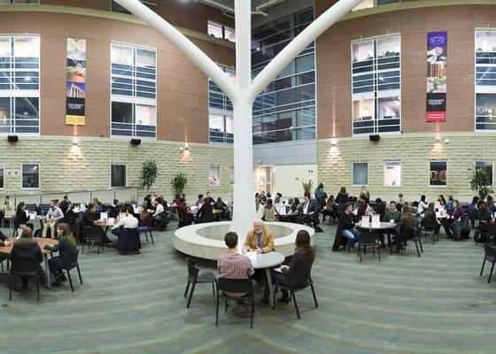 Science atrium students around tables